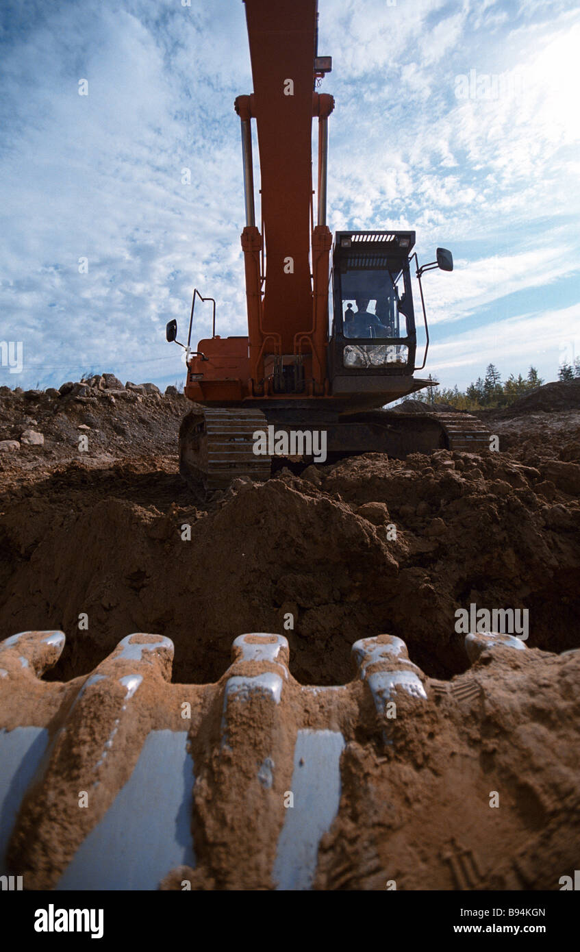 A digger excavating gold ore at the Bokovoye gold field of OOO Aldanzoloto Nizhny Kuranakh village - Stock Image