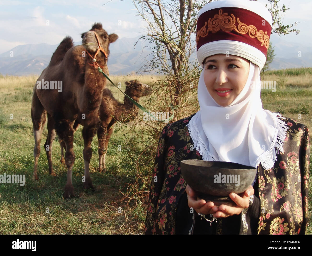 A Kyrgyz woman in folk dress offers guests a drink as her camels are grazing - Stock Image