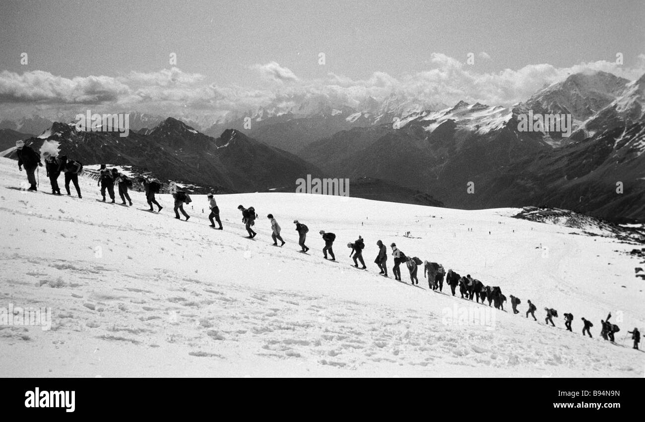 Travellers on the way to the Refuge for Eleven Holidayers high mountain hotel in the Caucasus - Stock Image