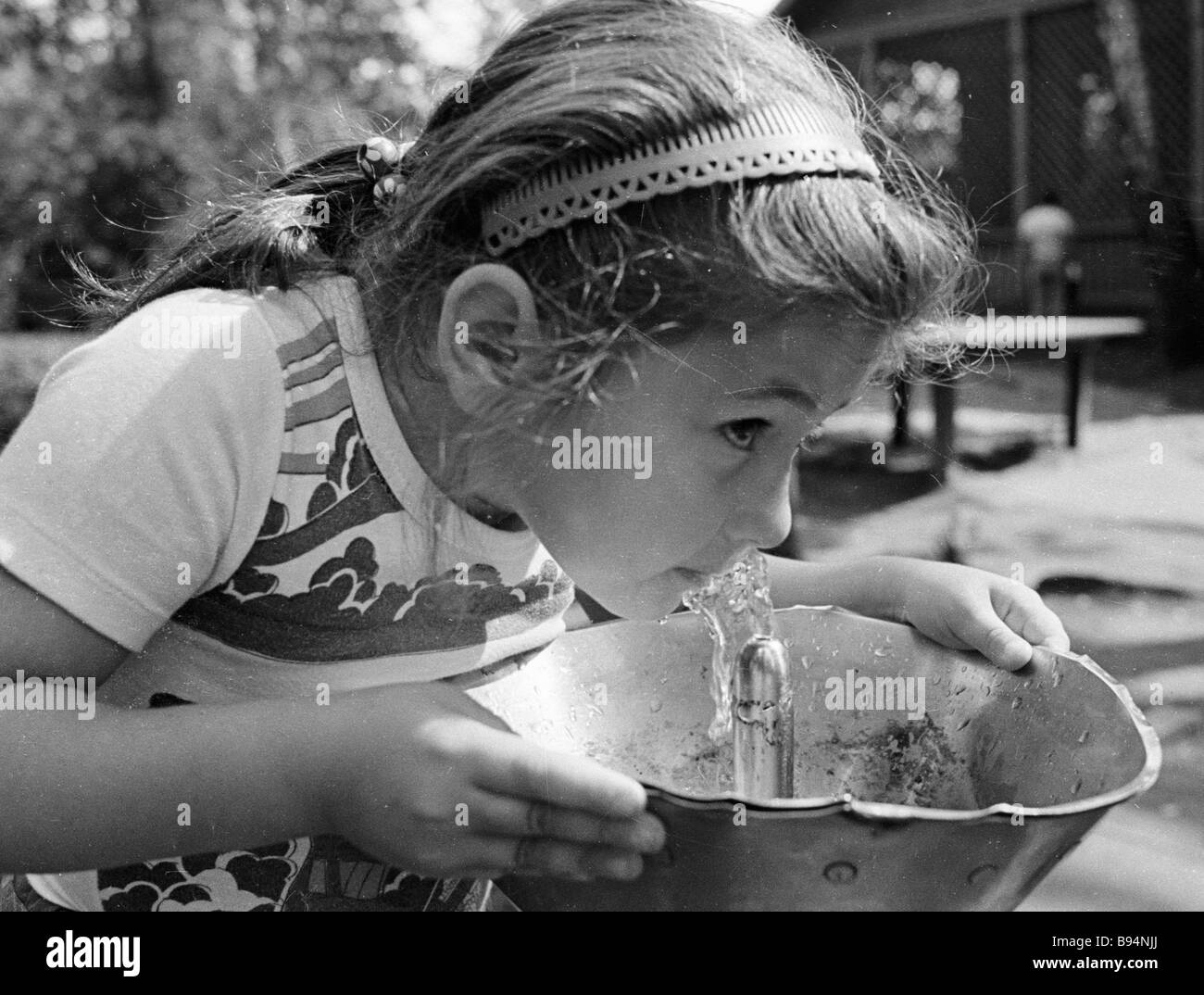 A girl drinking water from a street bubbler Supply of pure artesian water in the city of Electrostal was ensured - Stock Image