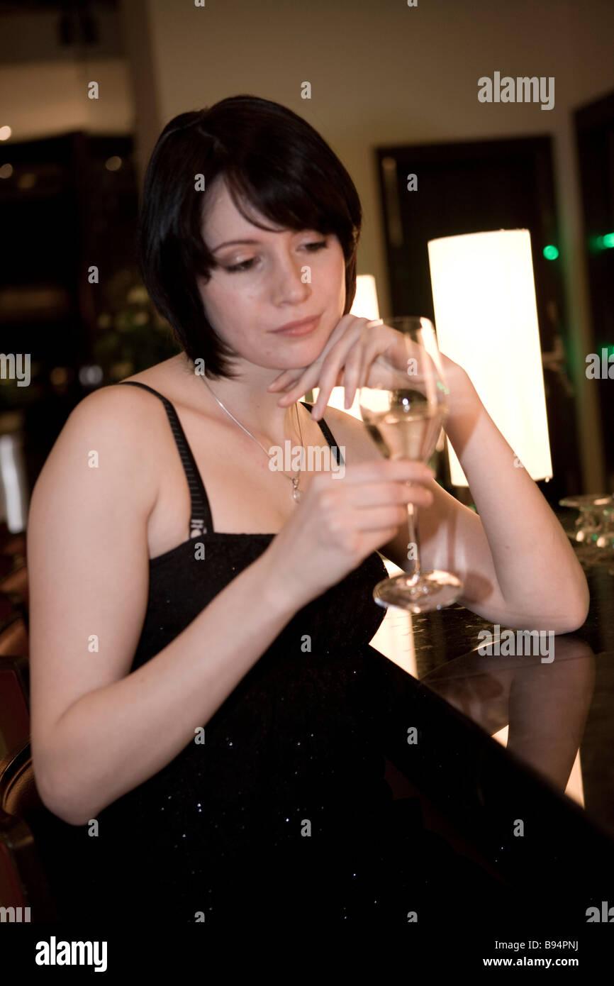 frau trink alleine an der hotelbar alkohol - Stock Image
