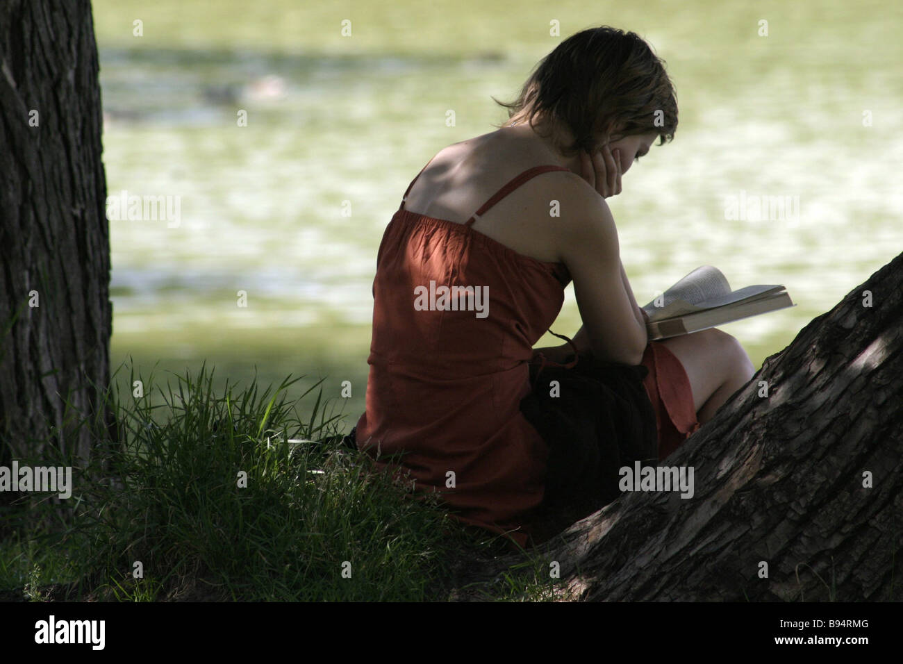 A girl engrossed in reading in a Moscow public garden - Stock Image