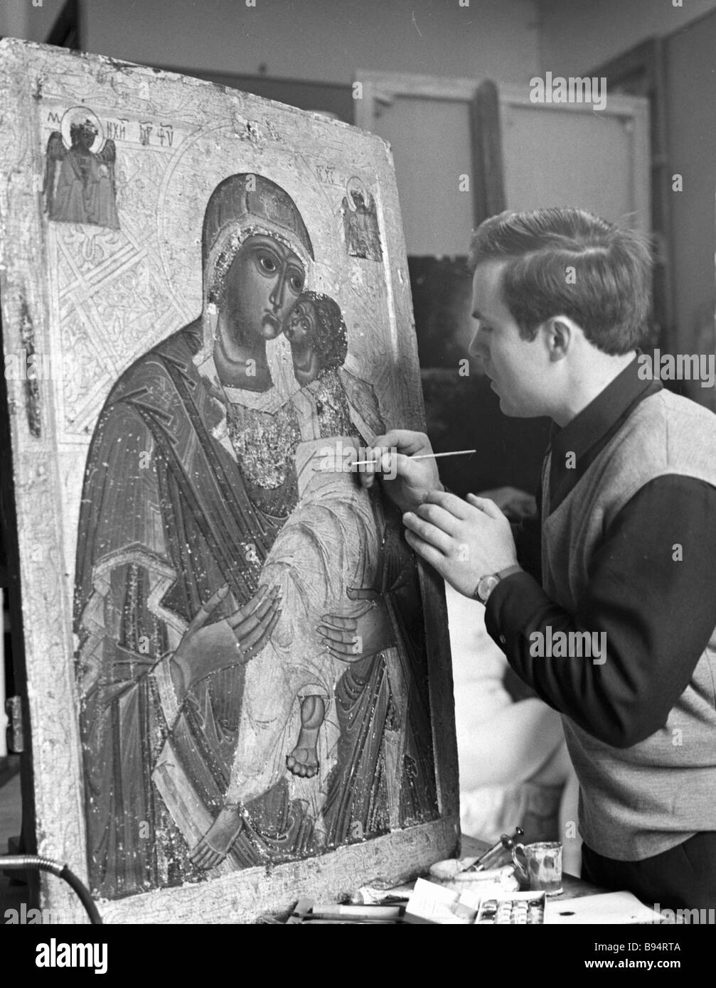 Artist restorer working on fifteenth century icon Tender Mercy which was found by an expedition to Volyn - Stock Image