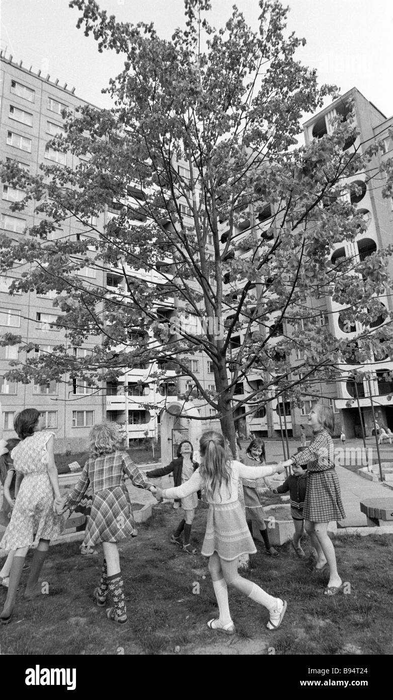 Children in merry go round around a trees in the year of a new housing development - Stock Image