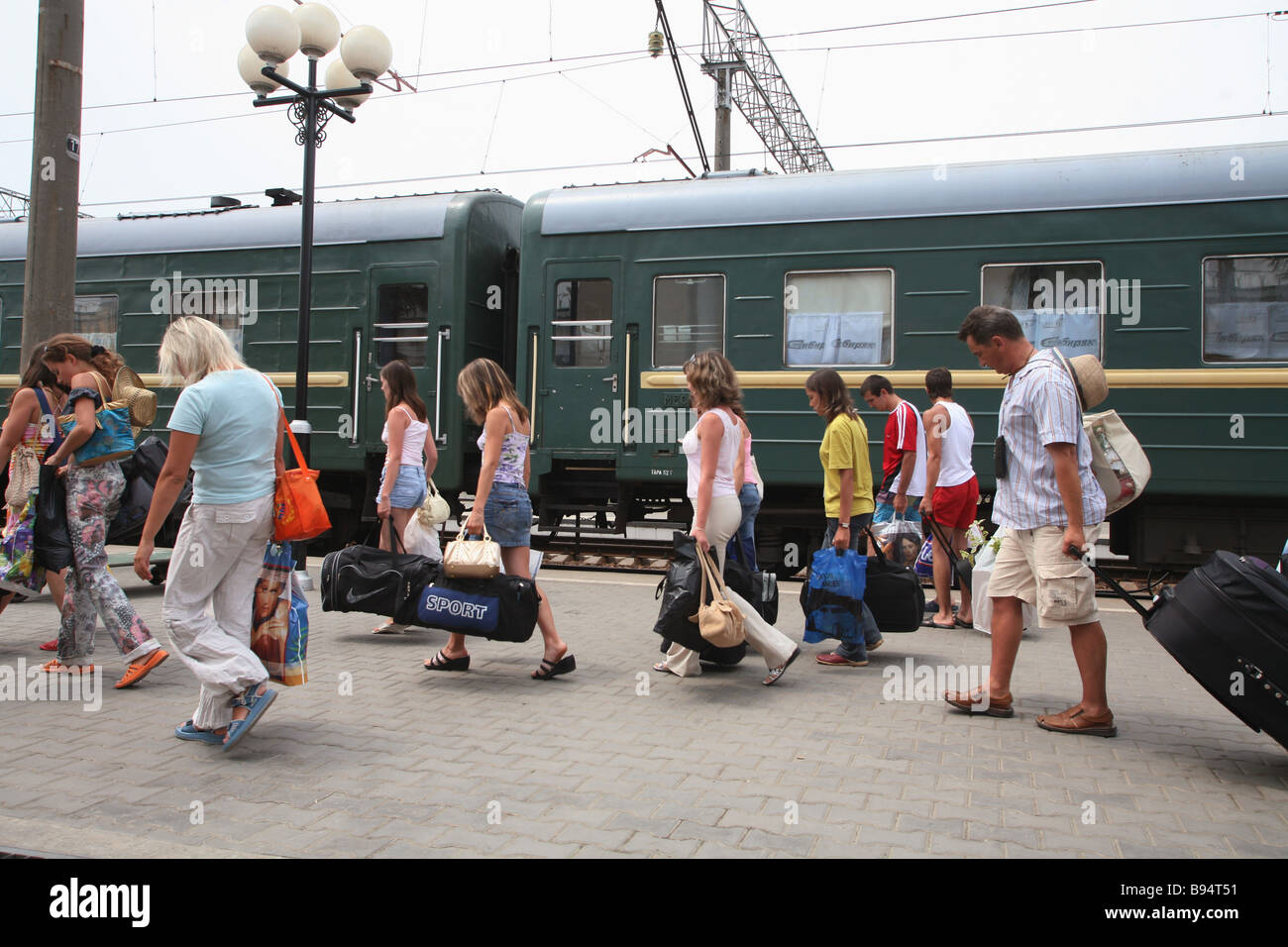 Vacationer passengers on the platform at the railroad terminus of Adler suburbia of Sochi posh Black Sea coastal - Stock Image