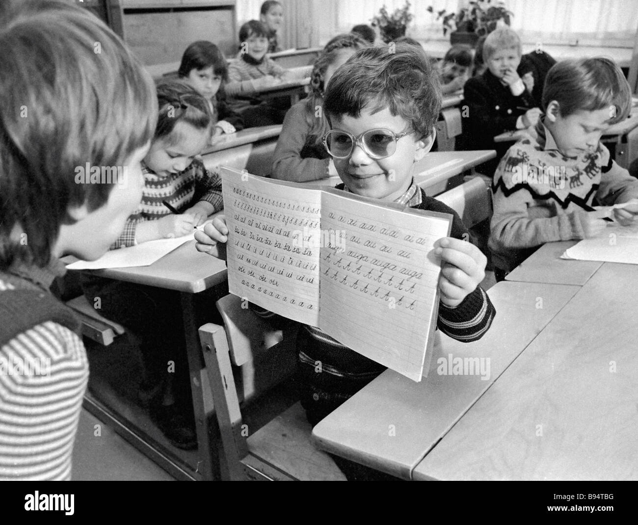 A zero grade pupil showing his notebook to a classmate at secondary school 2 - Stock Image