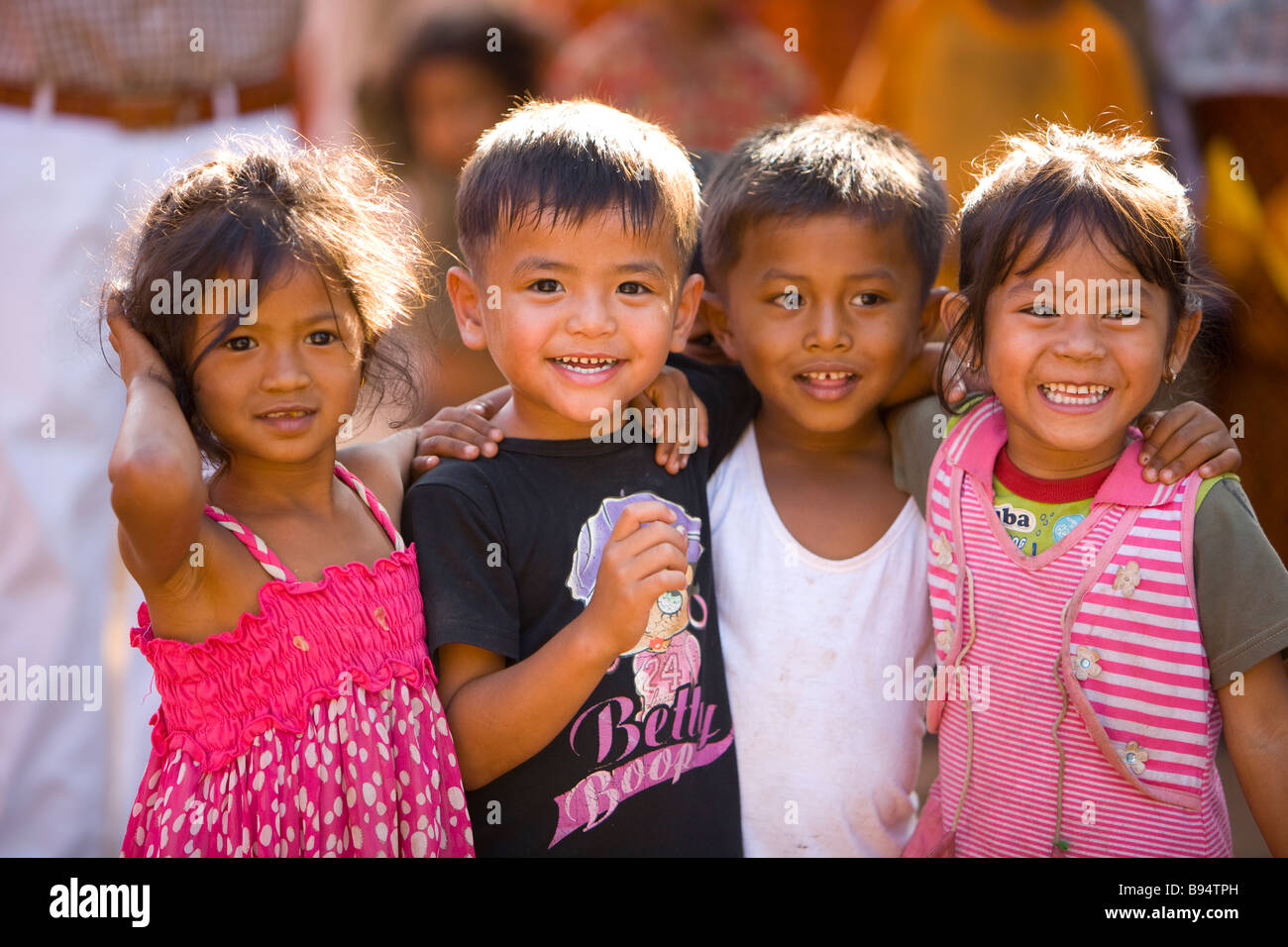 4 cute cambodian kids smiling at an island village in the mekong