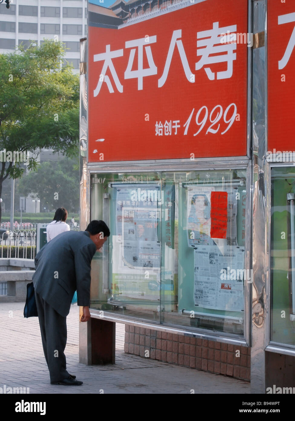 Many in the city customarily begin their day with reading morning newspapers on the stands - Stock Image