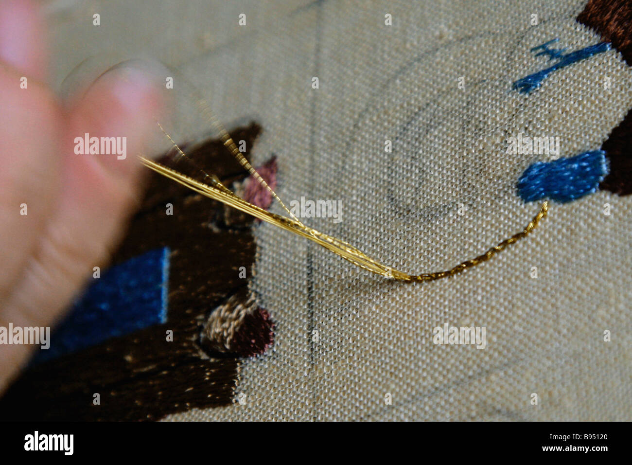 Seamstress using golden threads to make Vologda panel depicting Spaso Kamenny Monastery Vologda city - Stock Image