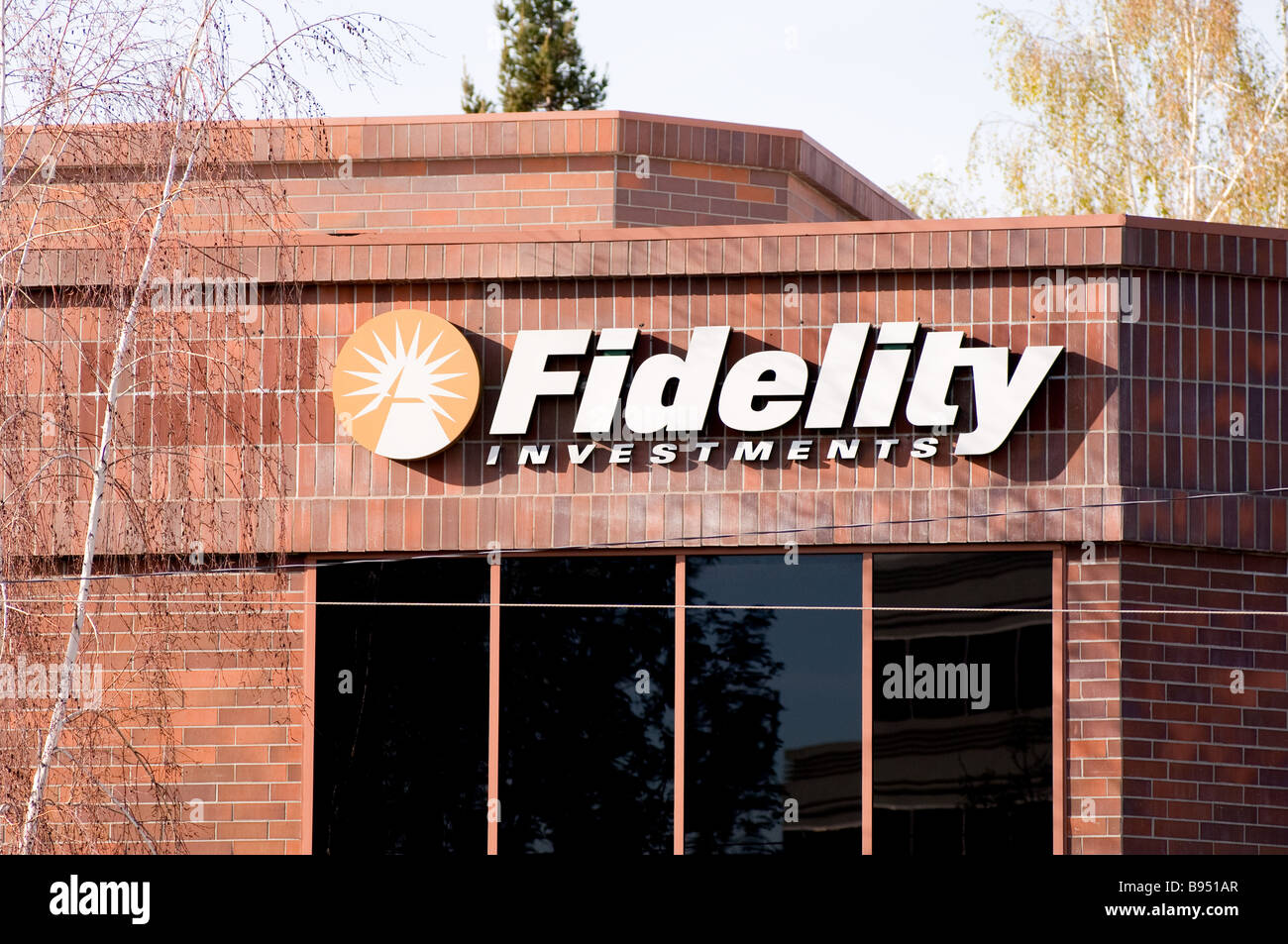 Exterior sign on the outside of brick building showing Fidelity Investments sign and logo - Stock Image