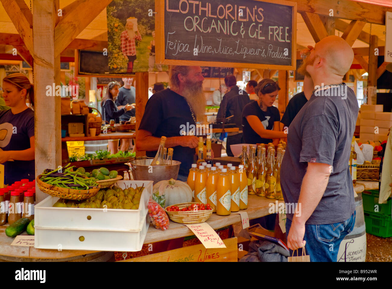 A customer samples fruit wine at the Mataka Farmer Marker Fruit wine, liqueur and produce stand. - Stock Image