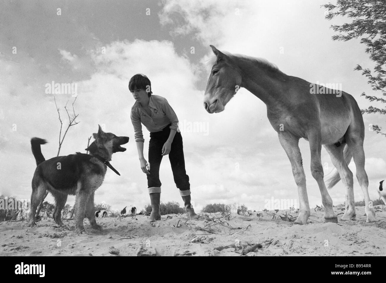 Ira the youngest daughter of an agricultural cooperative owner Nikolai Sivkov plays with home pets - Stock Image
