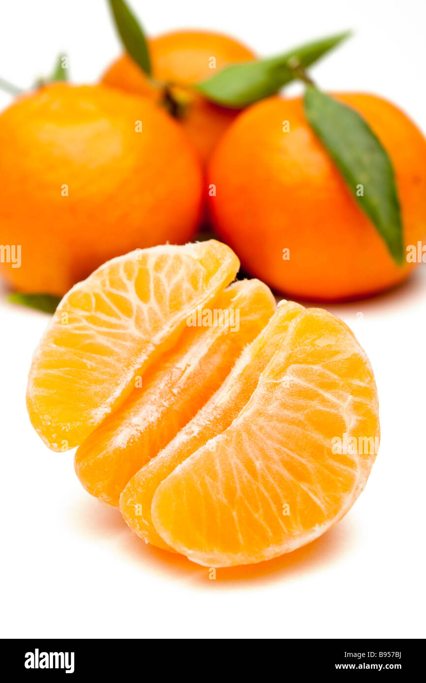 Peeled and whole mandarins with leaves - Stock Image
