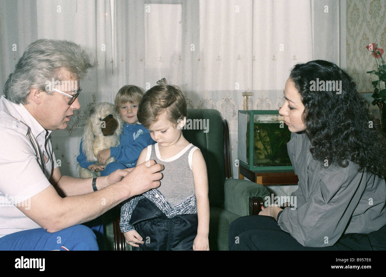 Psychic Alan Chumak left is conducting a healing session with a child - Stock Image