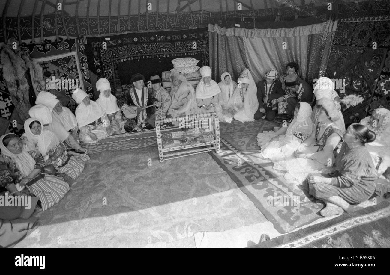 Kazakh people listen to a folk bard in a yurt - Stock Image