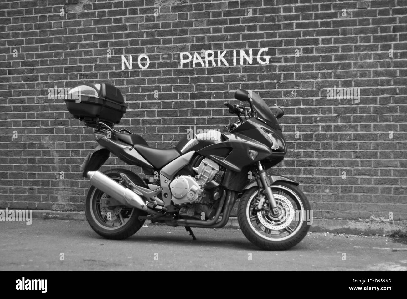 Motorcycle parked in a space labeled 'No Parking'. - Stock Image