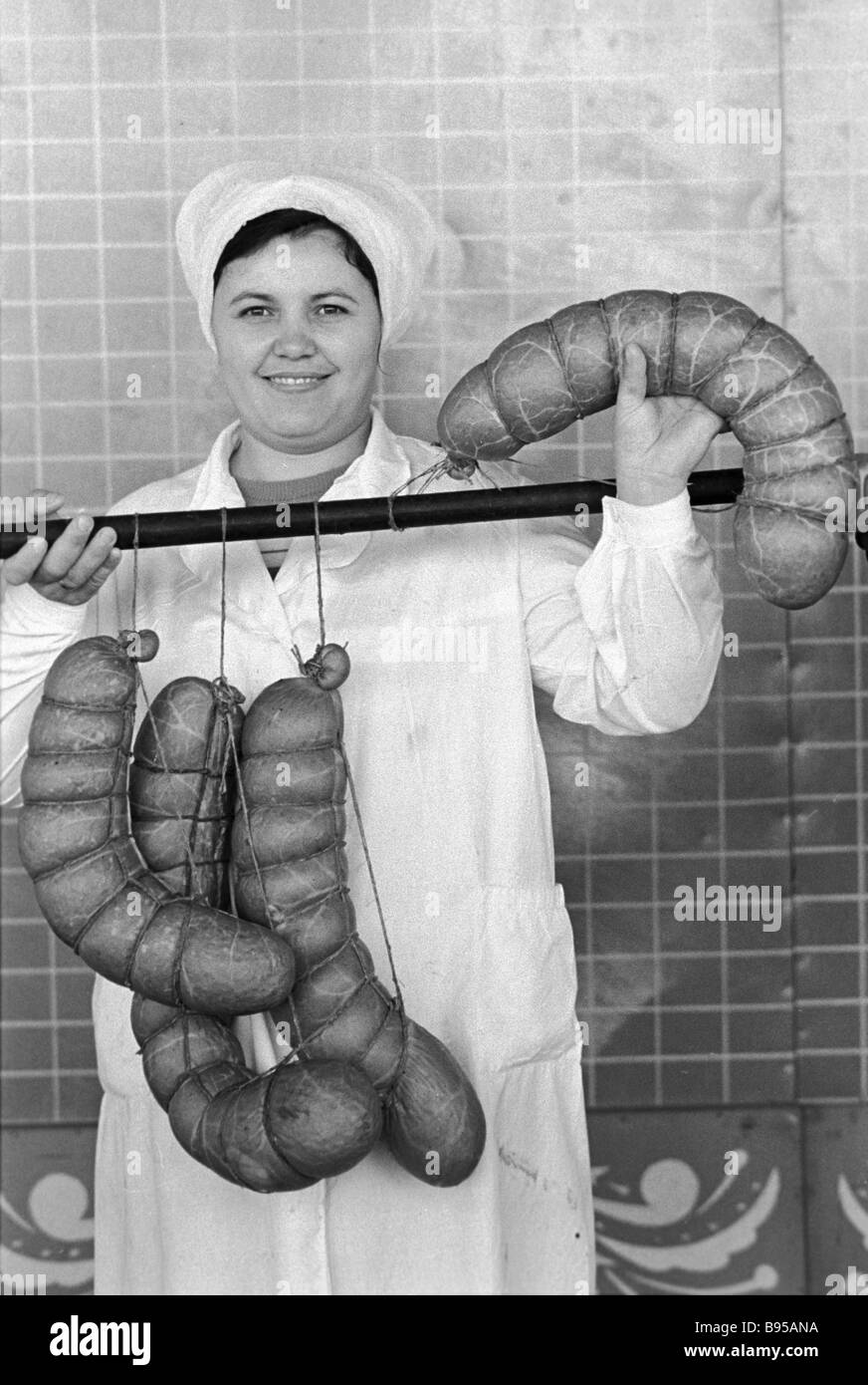 A worker at the Budennovsk poultry processing and meat packing house shows the sausage produced - Stock Image
