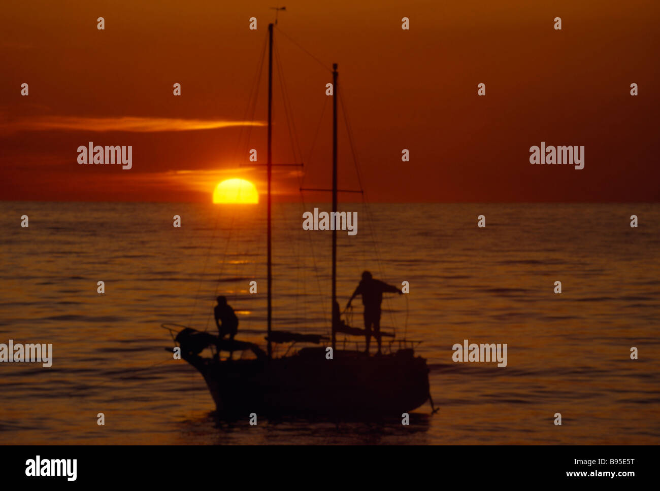 Wales Cardiganshire Borth Sailing Yachting Two people in silhouette on yacht at sunset with red sky and a low sun - Stock Image