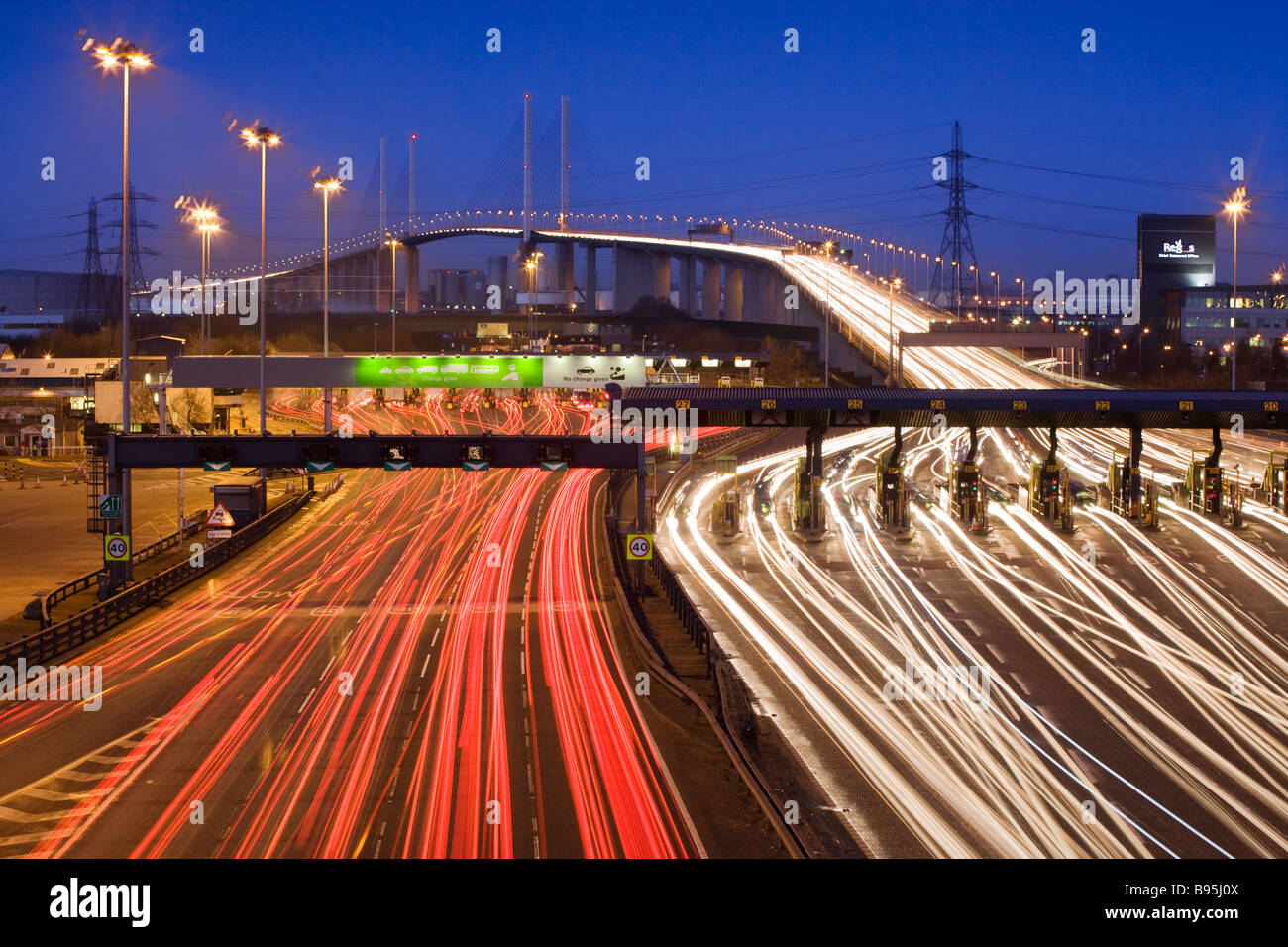 Traffic passing through toll booths at night. Queen Elizabeth II Bridge and Dartford Tunnel, Kent, UK - Stock Image