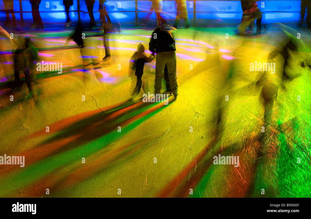 Germany, Bavaria, Munich. Ice skaters in motion blur with multi coloured light on a Winter ice rink in the city - Stock Image