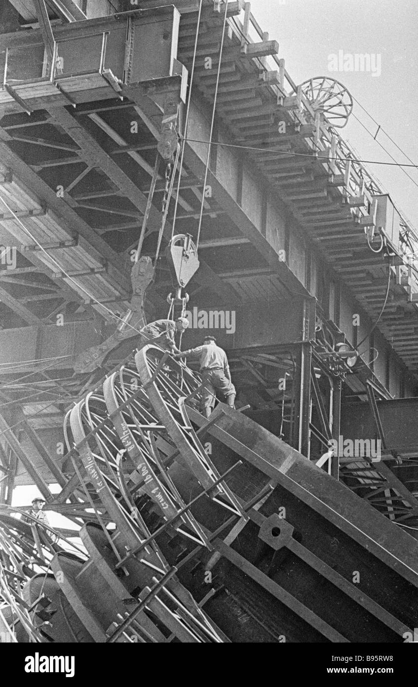 Workers assembling with a winch part of a concrete pouring crane on the construction of the Bratsk HEPP - Stock Image