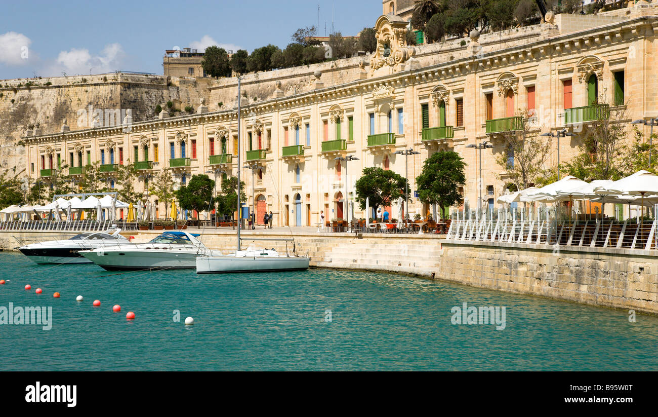 MALTA Valletta Boats at dockside in marina by restored waterfront old Baroque Pinto Warehouses below bastion walls - Stock Image