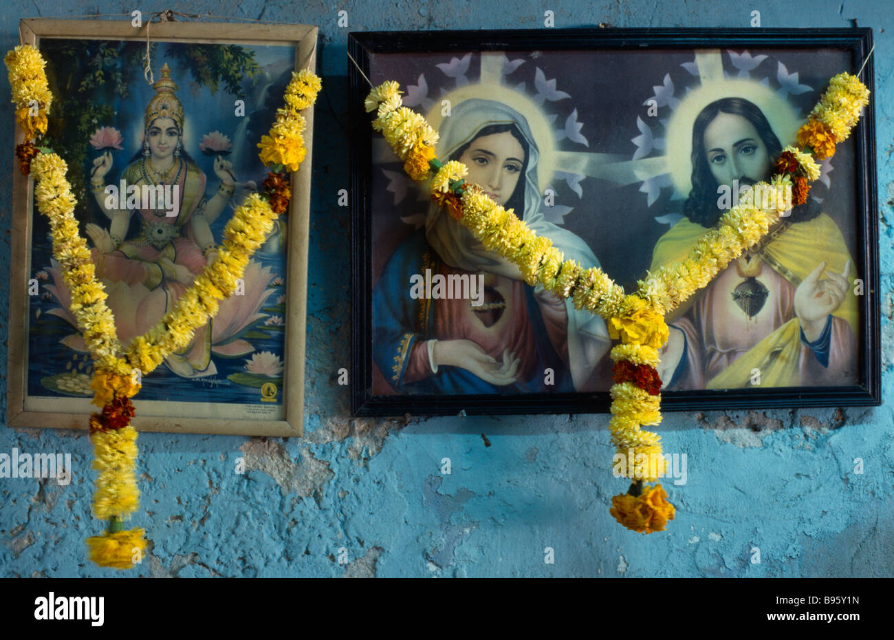 INDIA Religion Christian / Hindu Framed pictures of Hindu and Christian iconography hung with marigold flower garlands. - Stock Image
