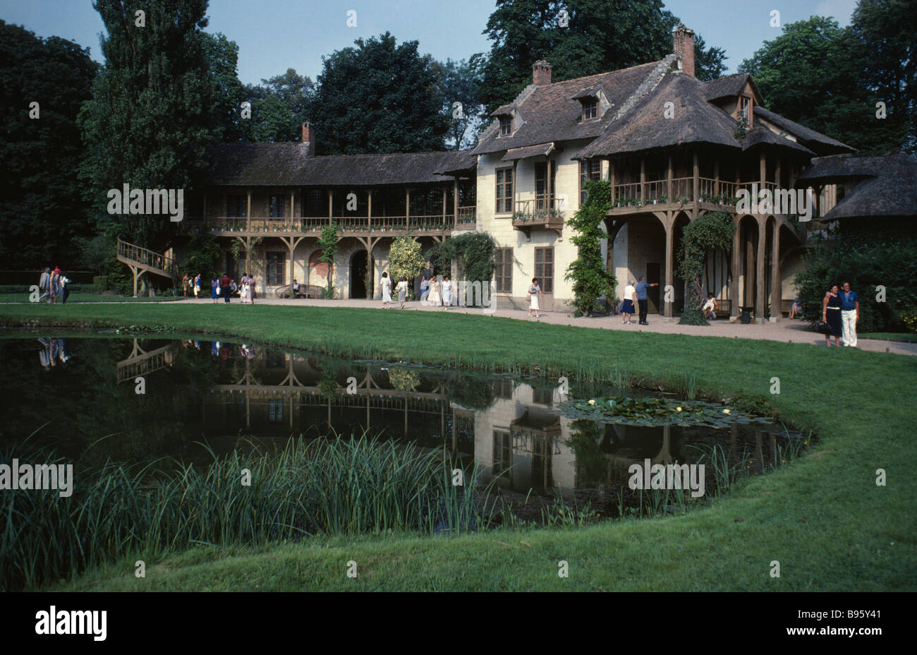 FRANCE Ile de France Paris Versailles Palace The Queens Cottage in the Hamlet exterior with tourist visitors reflected - Stock Image