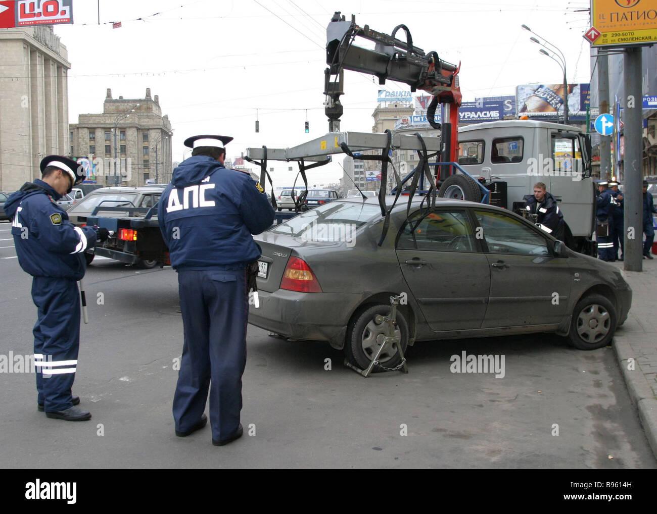 Traffic policemen removing parked cars blocking traffic on Smolenskaya Square - Stock Image