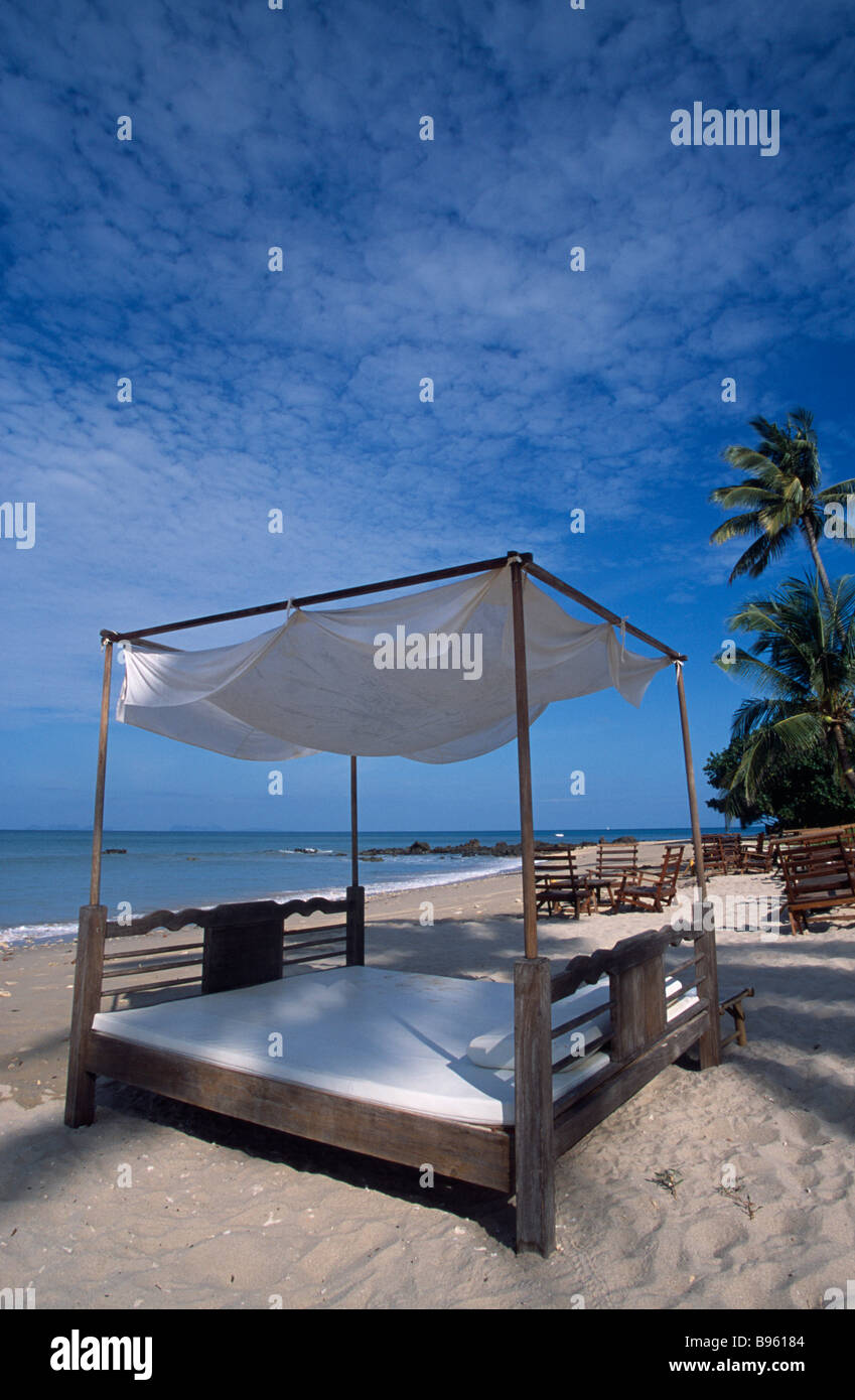 THAILAND Krabi Province Koh Lanta Yai Relax Bay Beach Four poster bed and table and chairs on coconut tree lined - Stock Image