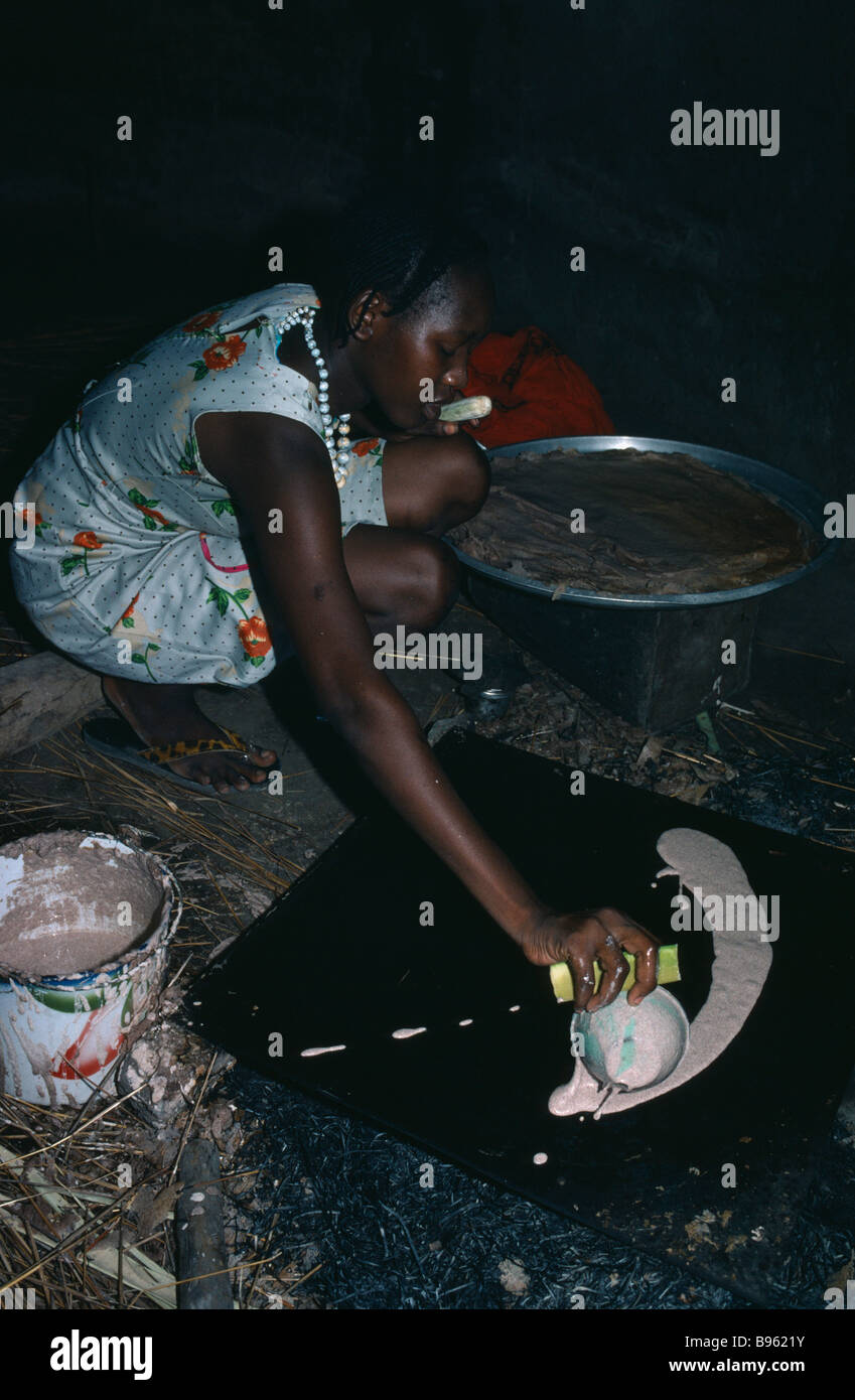 SUDAN Horn of Africa Food Cooking Dinka tribeswoman making flat bread on hotplate over fire inside hut. - Stock Image