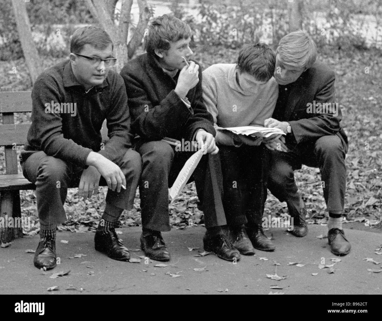 Young poets reading copies near the building which houses Yunost magazine editorial office - Stock Image