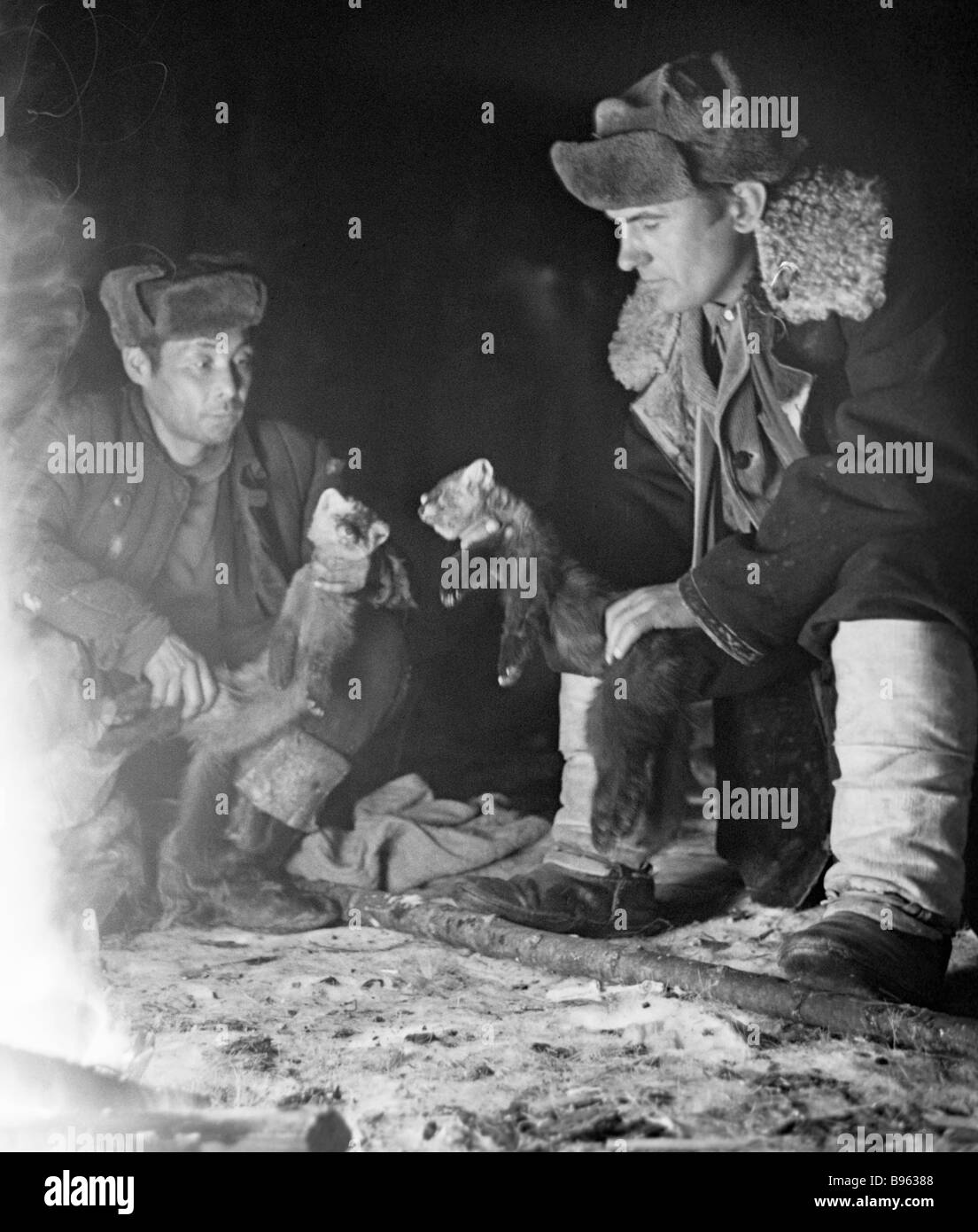 Hunters inspect their take near fire Eastern Sayan - Stock Image