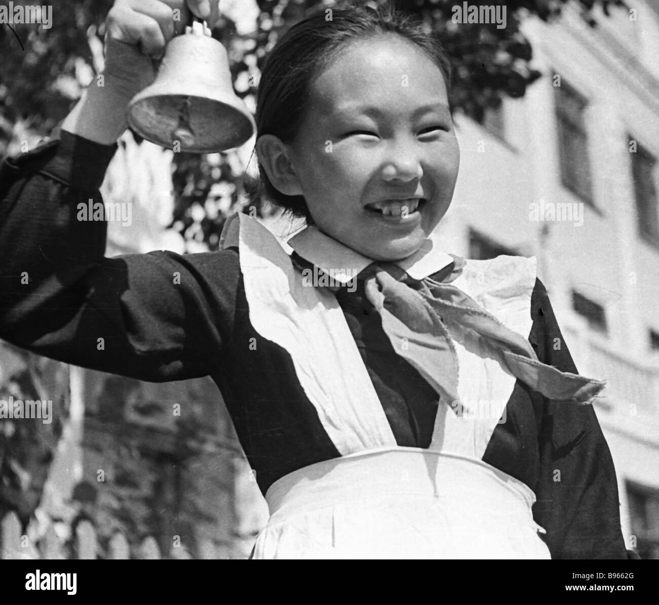 A Pioneer wearing a parade uniform tolls the bell on the last day of school - Stock Image