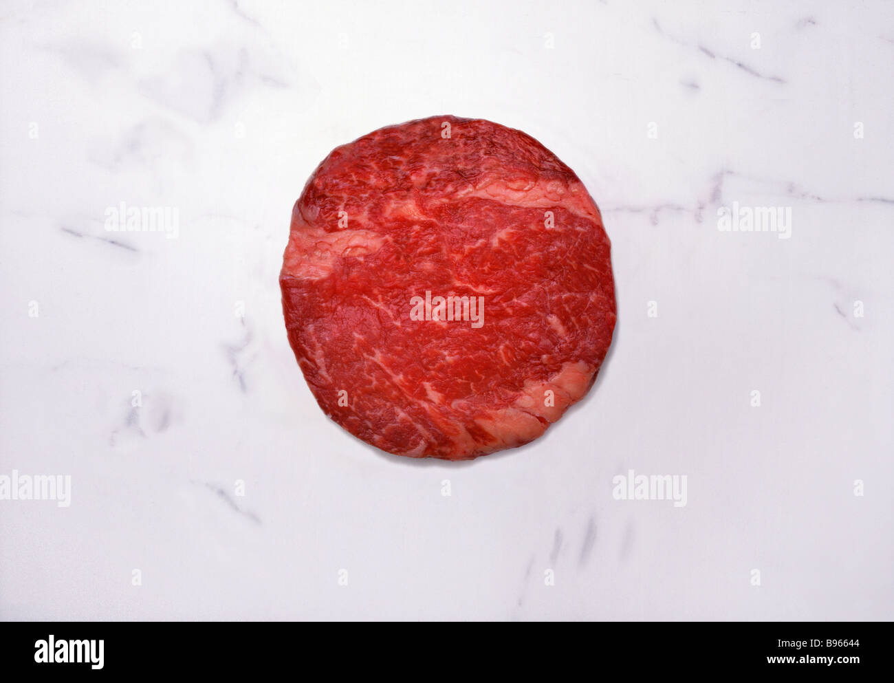Round raw beef on a marble slab Stock Photo