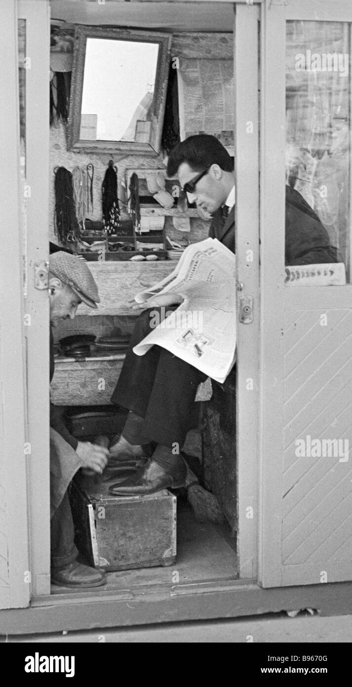 A shoeblack plying his trade - Stock Image