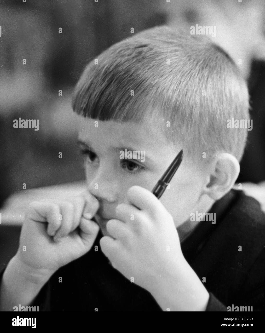 Boy listening to the teacher at the lesson - Stock Image