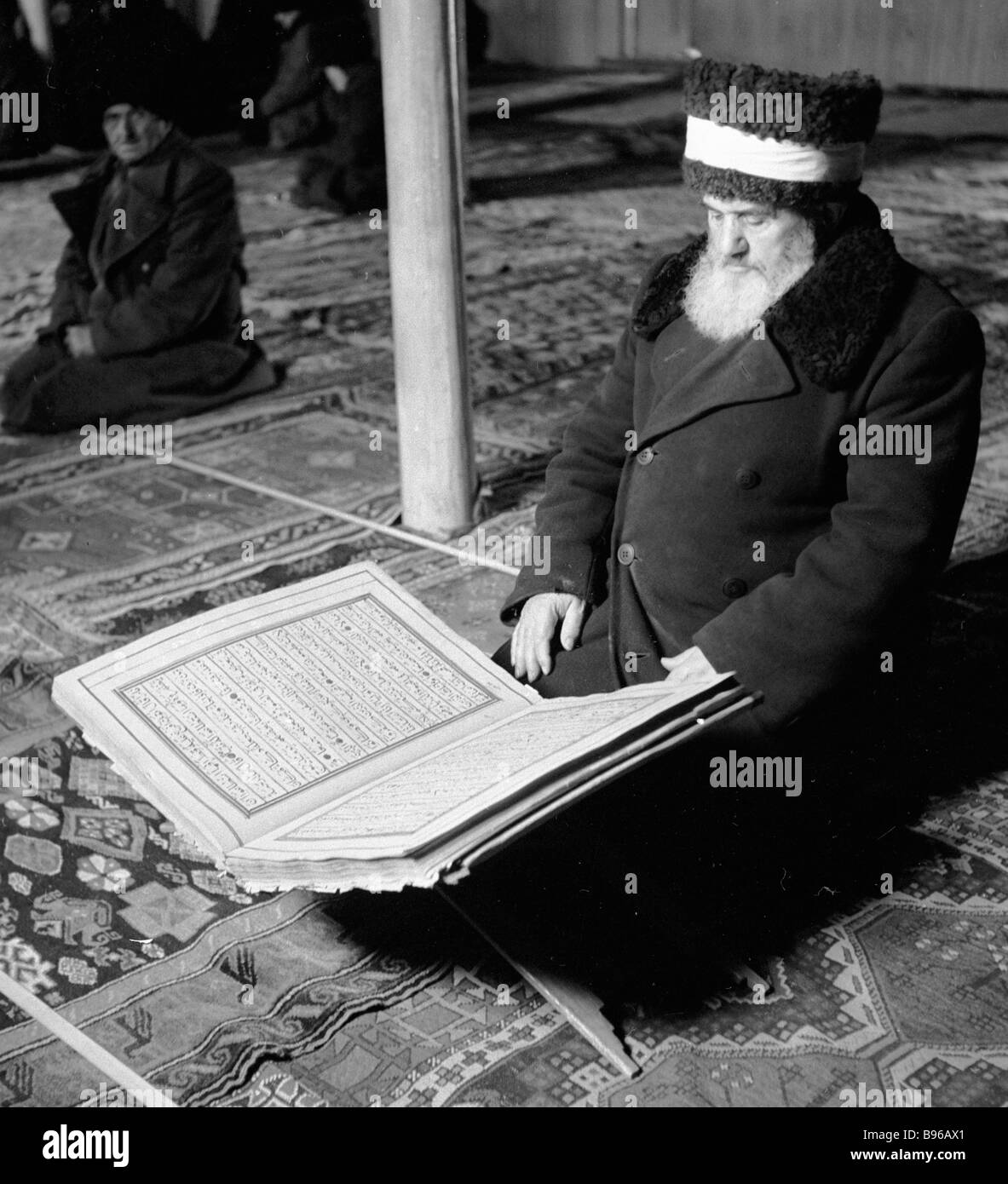 An imam reading the Koran in a mosque - Stock Image