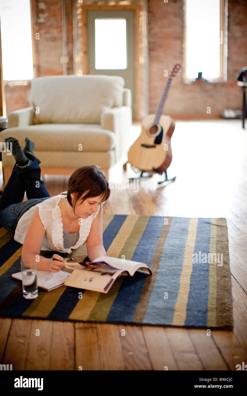 Young woman studying in urban loft - Stock Image