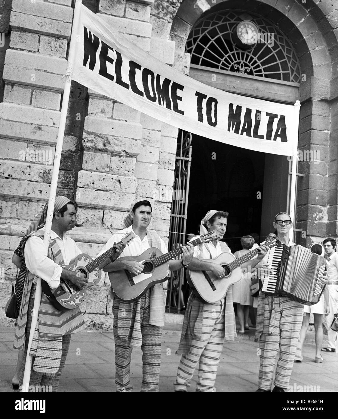 The Maltese in ethnic costumes greeting tourists with songs accompanied by guitar and accordion - Stock Image
