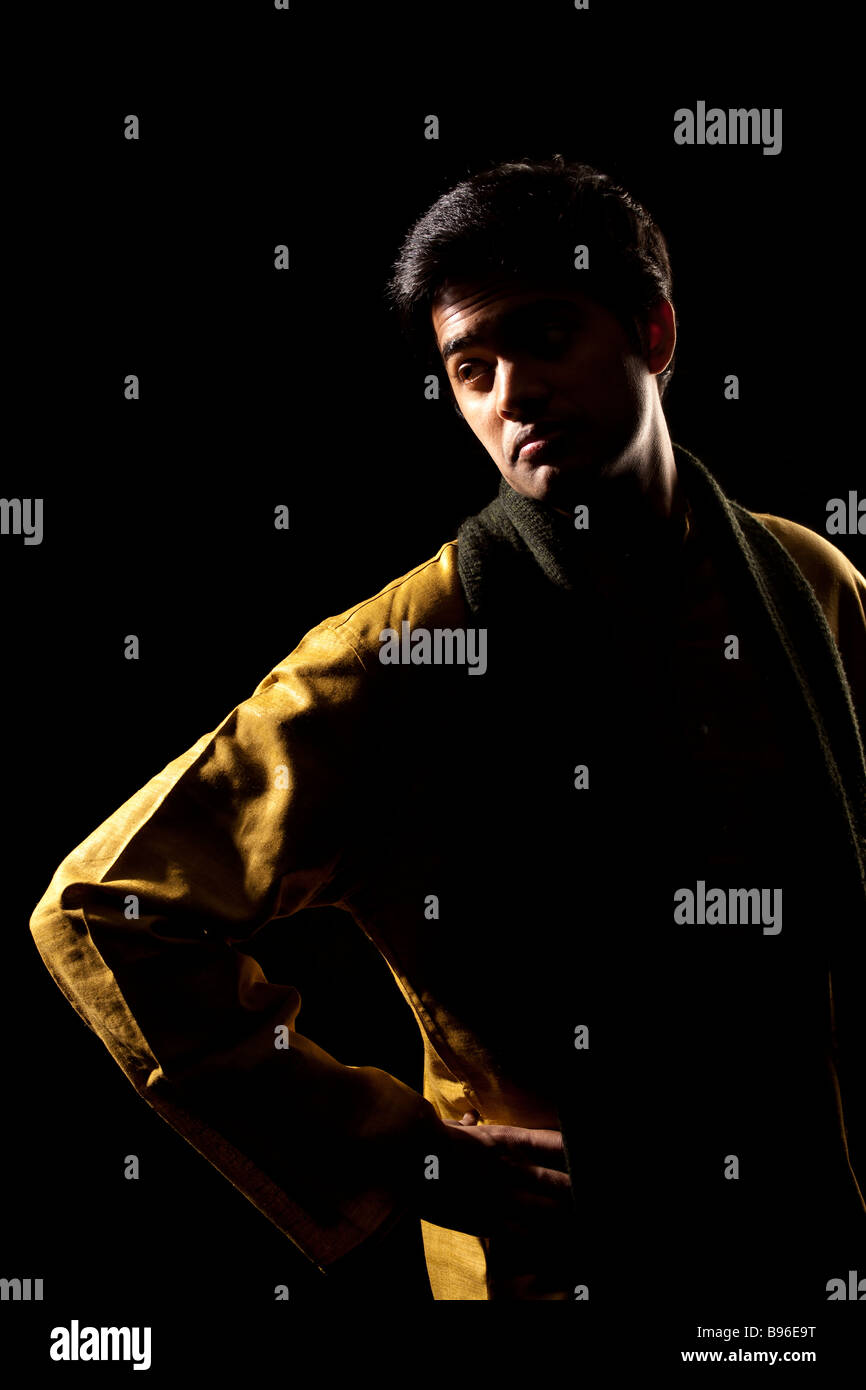 Handsome indian man on black background - Stock Image