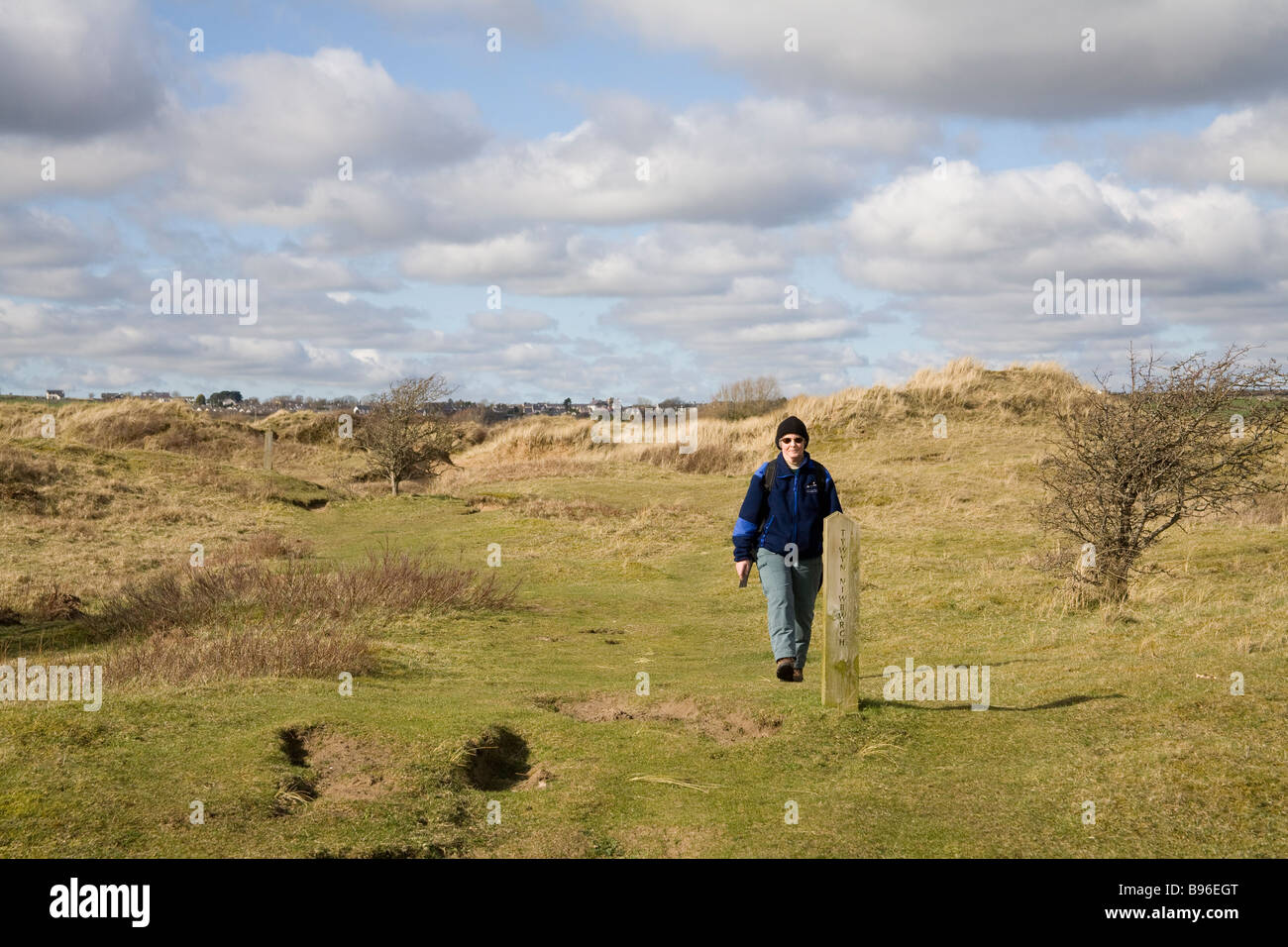 Newborough Anglesey North Wales March A woman walking along a waymarked footpath in Newborough Warren National Nature Stock Photo