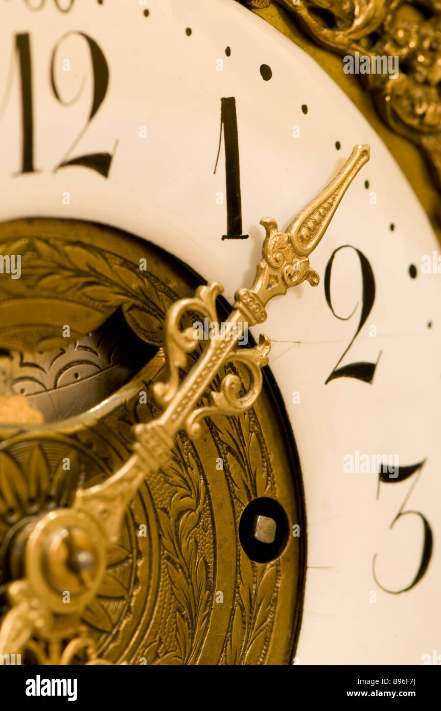 Close up of hand on clock face between one and two Stock Photo