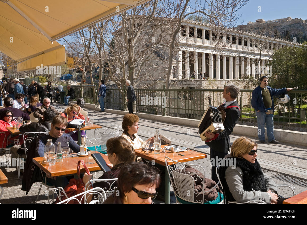 A busker entertains Athenians and tourists at a street cafe on Adrianou street, between Plaka and Monastiraki Central - Stock Image