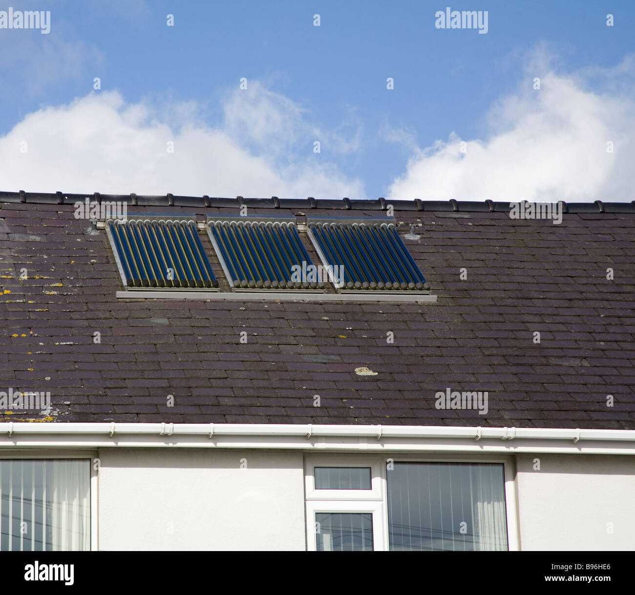North Wales March A set of three evacuation tube solar panels on the roof of a house to provide cheap renewable - Stock Image
