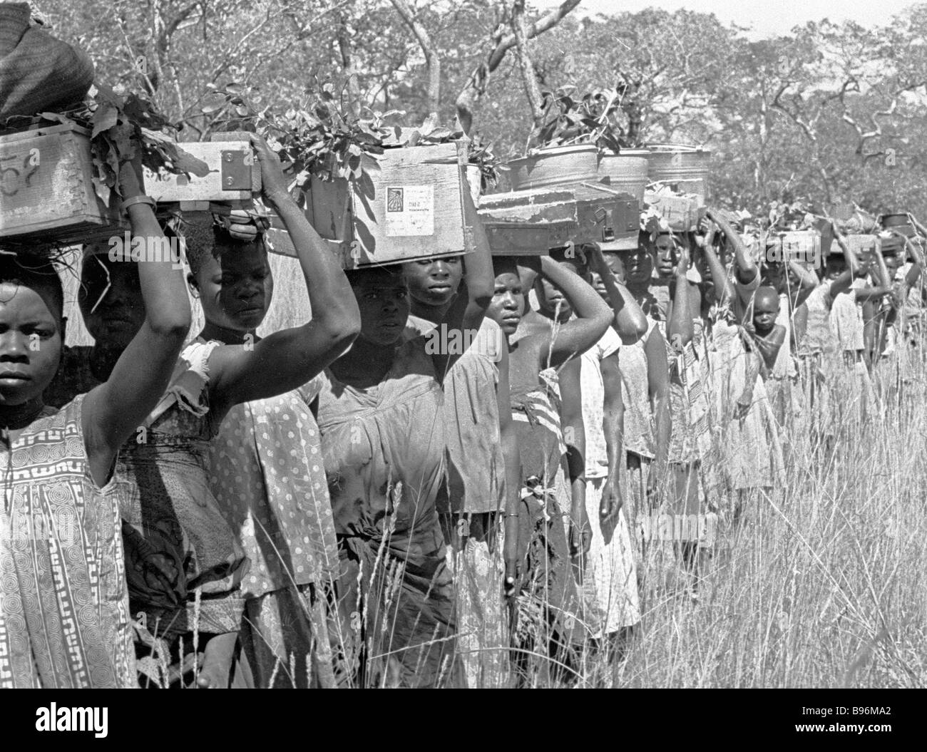 Caravan porters delivering arms ammunition clothes and medicine to a FRELIMO guerilla base - Stock Image
