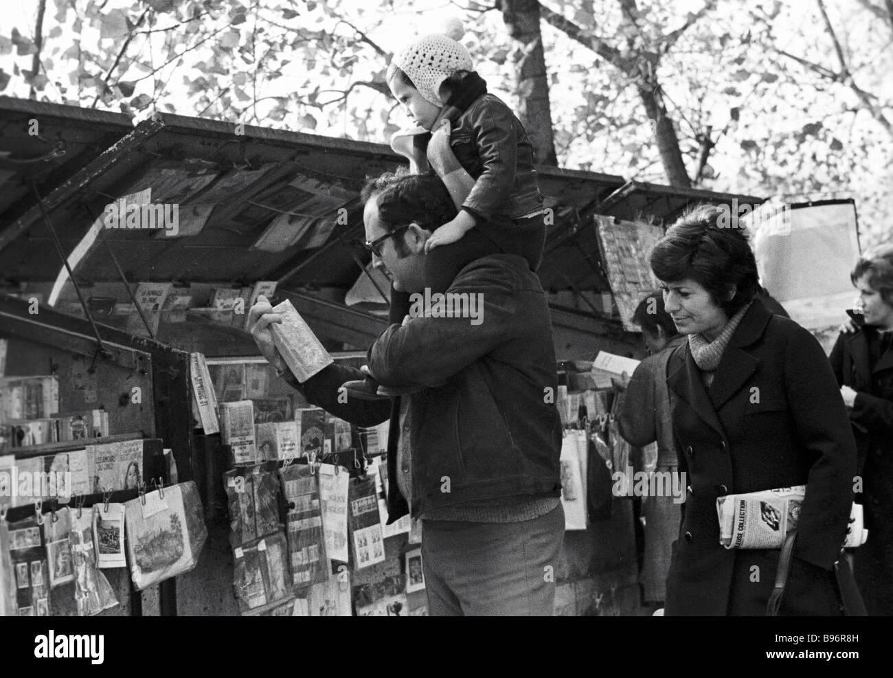 Parisians looking at rare books on the Seine embankment - Stock Image