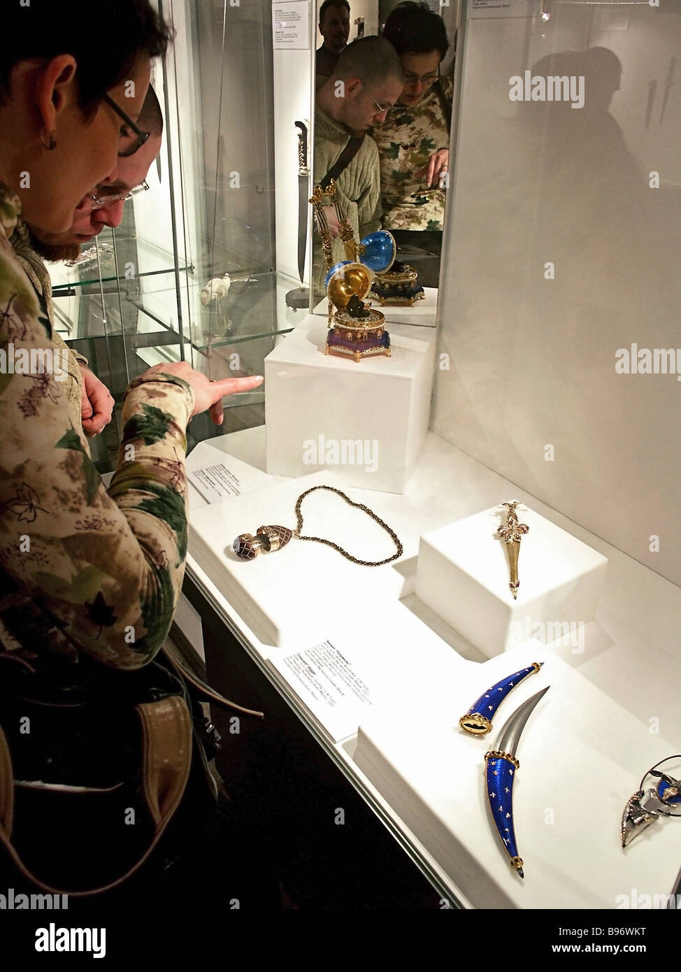 Visitors admire showcase with knives during exhibition Russian Blades 2004 at the Moscow Kremlin s Assumption Belfry - Stock Image