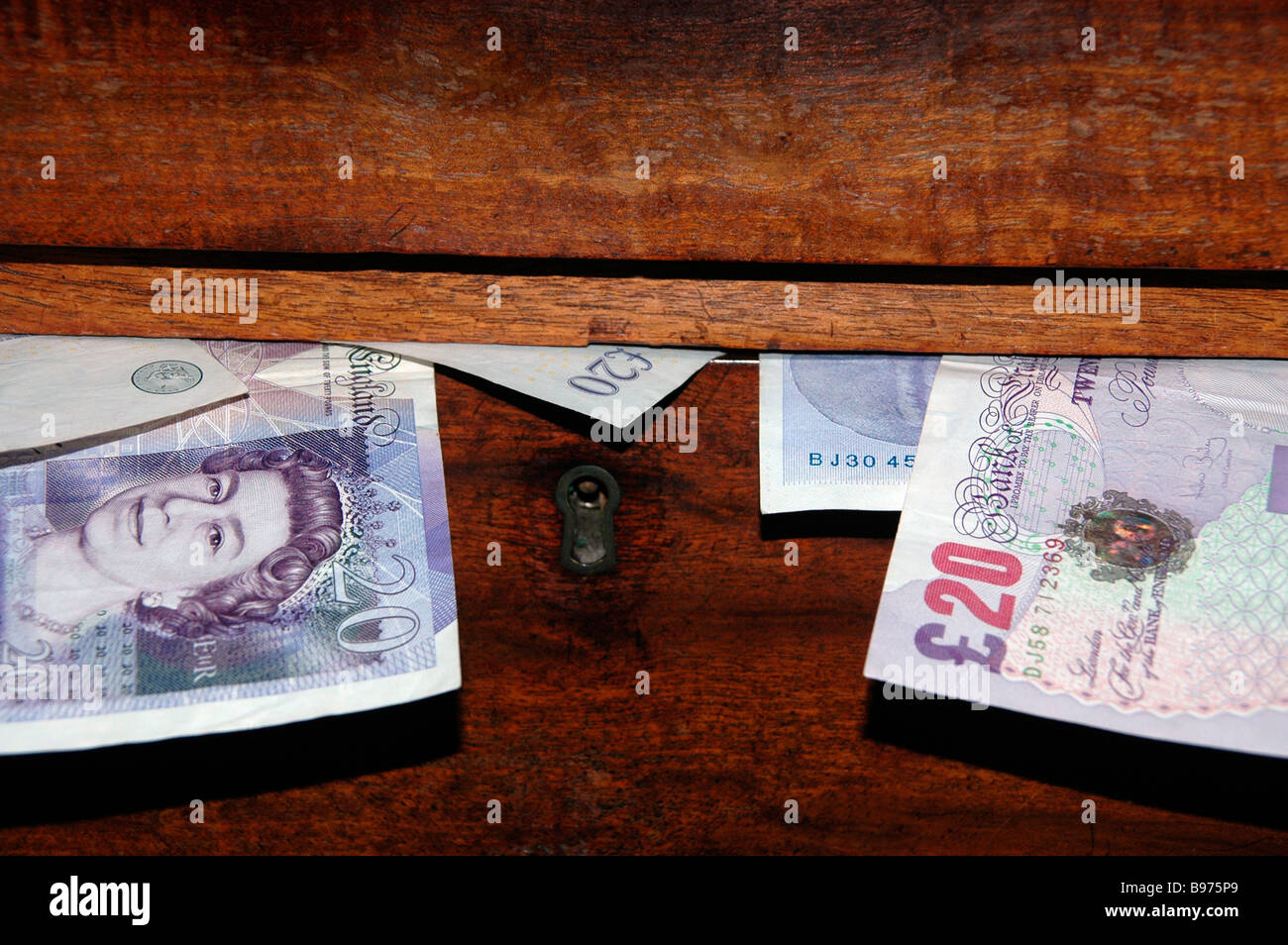 A locked drawer with 20 pound notes bulging out. - Stock Image
