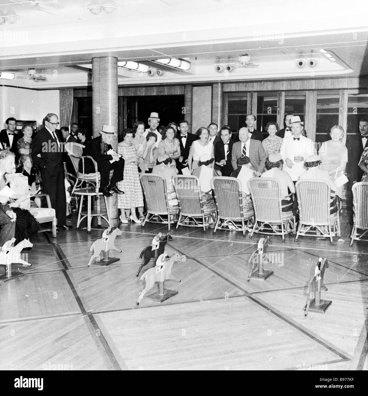 Passengers on a 1950s cruise ship, The British India playing horse racing game on deck. - Stock Image